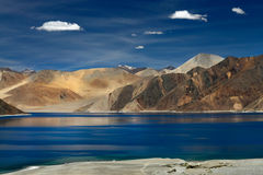 High mountains of Lake Pangong: dark blue water, bright brown mountains and cirrus clouds in the sky, a summer trip through the Hi Royalty Free Stock Photo