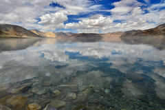 High mountains Pangong lake: the lake is clear and blue surface, calm as a mirror and reflects the many clouds and blue sky in the Stock Photos