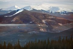 High mountains with snowy peaks at sunset. Mountain tops in the snow, panorama of mountain slopes and hills at sunset Stock Photos