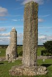High North Cross. Clonmacnoise. Ireland. The north cross and the round tower of the finian temple at a distance. Medieval monastery of Clonmacnoise. Ireland Stock Photo