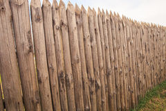 high old wooden fence of logs in form of palisade Royalty Free Stock Image