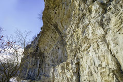 High overhanging cliff wall framing a narrow hikiing path in win stock photo