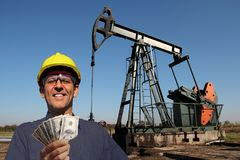 High Paying Jobs Concept. Oil worker or petroleum engineer holding US dollar bills in front of oil well. Best paid jobs concept royalty free stock photography