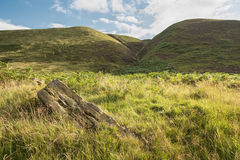 High Peak, Derbyshire, England. A view of the High Peak area of the Peak District with a rock in the foreground Royalty Free Stock Images