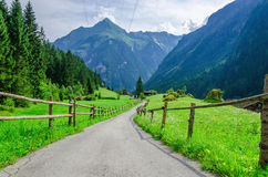 High peaks of the Alps with coutry road,  Austria Royalty Free Stock Photography