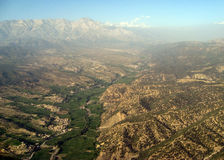 High Peaks Rise Above the Haze Near Pakistan. The rugged peaks of the Tora Boras rise above the smog and haze of an isolated farming valley that heads east into royalty free stock photos