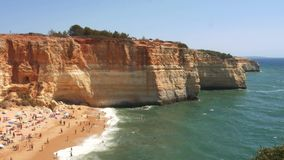 High perspective panning of gold-coloured cliffs, busy beach and turquoise ocean in Benagil beach, Lagoa, Algarve. Portugal stock video footage