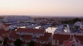 High perspective timelapse of sunset at Vilamoura Marina, Algarve, Portugal with busy nightlife around the Marina full. Of shops and restaurants stock video footage