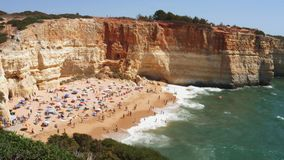 High perspective view of gold-coloured cliffs, busy beach and turquoise ocean in Benagil beach, Lagoa, Algarve, Portugal.  stock video footage