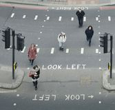 High perspective view of pedestrians in the City of London crossing the street. Iconic look left and look right signs. London, UK- Mar 13, 2018: High perspective Stock Photos