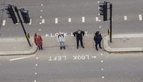 High perspective view of pedestrians in the City of London crossing the street. Iconic look left and look right signs. London, UK- Mar 13, 2018: High perspective stock photo