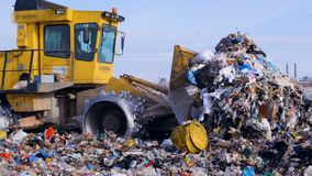 A high pile of trash moved by a landfill truck. Water, air contamination concept. A close view of a landfill compactor moving a large pile of assorted garbage stock video footage