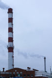 High pipe CHP on the background of blue sky, fog, smog Royalty Free Stock Photos
