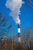 High pipe thermal power plant on the background of blue sky, fog, smog. Royalty Free Stock Photography