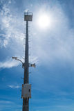 High pole with security camera and loudspeaker on blue sky Royalty Free Stock Photo