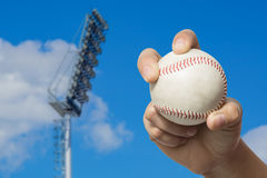High pole Spotlight Stadium lights. Hand holding a baseball on high pole Spotlight Stadium lights with blue sky background Royalty Free Stock Image
