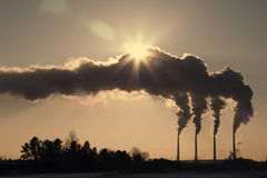 High pollution from coal power plant. Black smoke against sun. Smoking chimney of industrial buildings complex Stock Photos