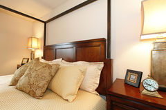 High posts bed with a beautiful beige bedding and nightstand. Cl Royalty Free Stock Photography