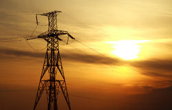 High power electric line towers at dramatic sunset Stock Images