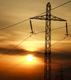 High power electric line towers at dramatic sunset Royalty Free Stock Photos