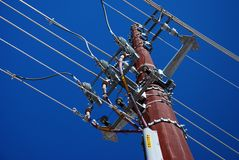 High Power Electrical Transmission Lines. High-voltage electrical transmission lines atop a rusted steel support bar shot against a clear blue sky Royalty Free Stock Image