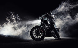High power motorcycle chopper with man rider at night. Fog with backlights on background stock photo