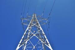 High power tower pole against blue sky