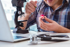 The high precision engineering with man working with microscope Stock Photos
