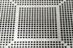 Close-up of used laser CNC high precision small pitch cut stencil for BGA chip reballing for electronics industry in partial focus stock image