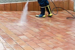 High pressure cleaner. Workers cleaning with high pressure cleaner the entrance of a car garage Stock Photo