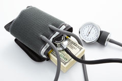High pressure financial situation. Apparatus to check blood pressure is used to measure financial pressure with stack of US$100 bills Stock Photo