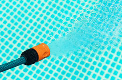 High pressure water from a hose flowing into a pool - closeup Stock Photos