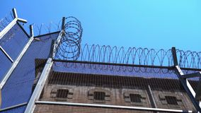 High prison fence with barbed wire against a clear sky. bottom view.  stock video