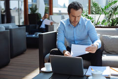 Smart serious businessman studying documentation. High professionalism. Smart serious handsome businessman holding a document and studying it while working in a Stock Image