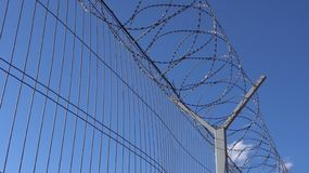 A high protective fence with barbed wire. royalty free stock image