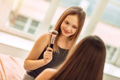 Cheerful girl showing makeup brush to her sister. High quality. Beautiful teenage girl sitting on the bed in front of her elder sister and showing her a makeup Royalty Free Stock Image