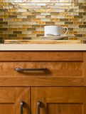 High quality cherry wood cabinets with bronze cabinet hardware, quartz countertops & glass tile mosaic backsplash in contemporary. A coffee cup rests on a royalty free stock photos
