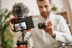 High quality. Close up of digital camera screen with blogger showing photo camera lens while recording new video review. For his vlog royalty free stock images