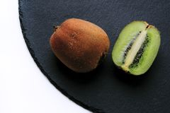 Fresh kiwis and black shale. High quality close up photo of chopped in a half kiwis on black shale dish, view from the top. Kiwis are one of the most popular Stock Images