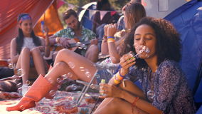 In high quality format carefree hipster blowing bubbles in tent. At a music festival stock video footage