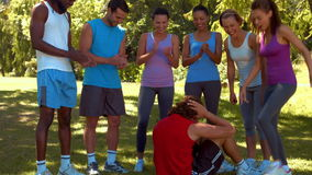 In high quality format fitness group encouraging man doing sit ups stock video footage
