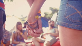 In high quality format hipster couple holding hands on campsite. At a music festival stock video footage