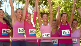 In high quality format smiling women running for breast cancer awareness stock video