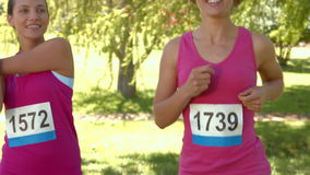 In high quality format smiling women running for breast cancer awareness