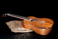 High quality hand-made koa wood ukulele. Traditional Hawaiian uk. E musical instrument on display against black background royalty free stock photo