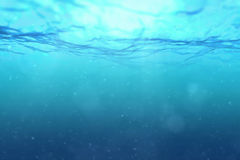 High quality perfectly seamless loop of deep blue ocean waves from underwater background with micro particles flowing. Light rays shining through royalty free stock photography