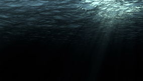 High quality perfectly seamless loop digital animation of deep dark ocean waves from underwater background. Light rays shining through, high definition 4k and