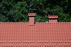 High quality red metal tile roof of a house. Against green trees background stock photos