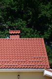 High quality red metal tile roof of a house. Against green trees background stock image