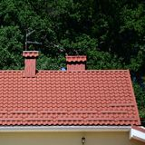 High quality red metal tile roof of a house. Against green trees background stock photo